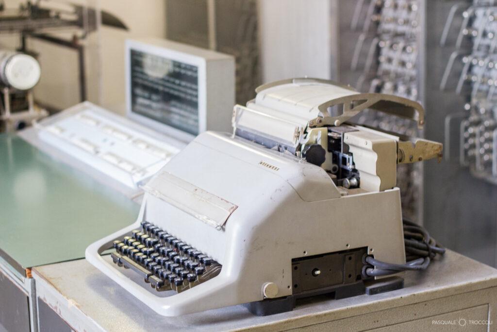 一个老式电传打字机,背后是看起来像电路板或是 CRT 显示屏